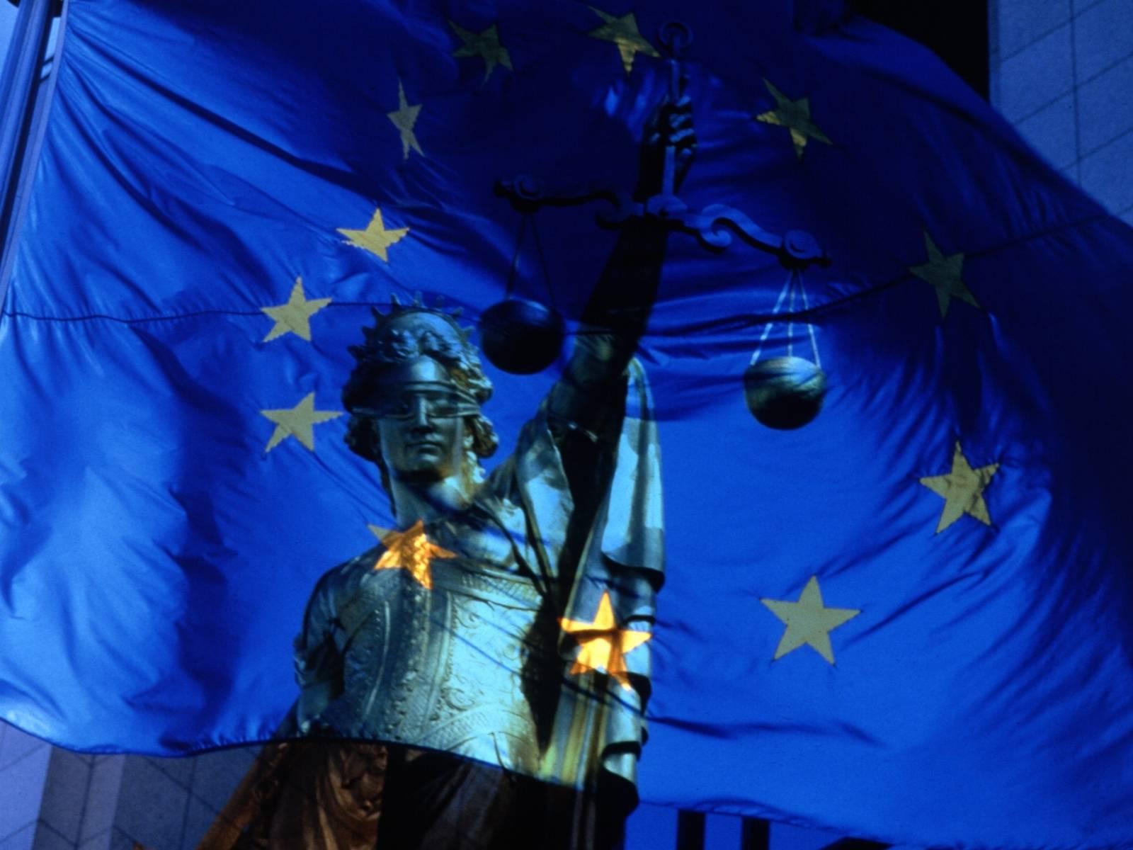 Justitia hinter einer durchsichtigen Fahne der EU