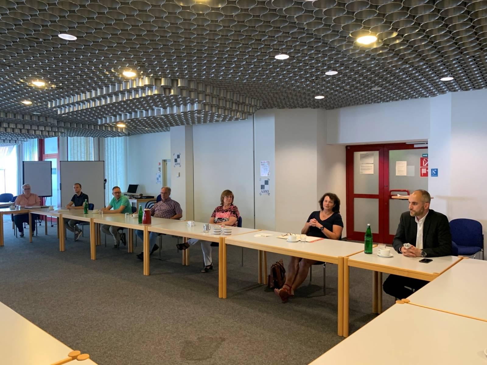 Mehrere Menschen an Tischen in einem Raum.