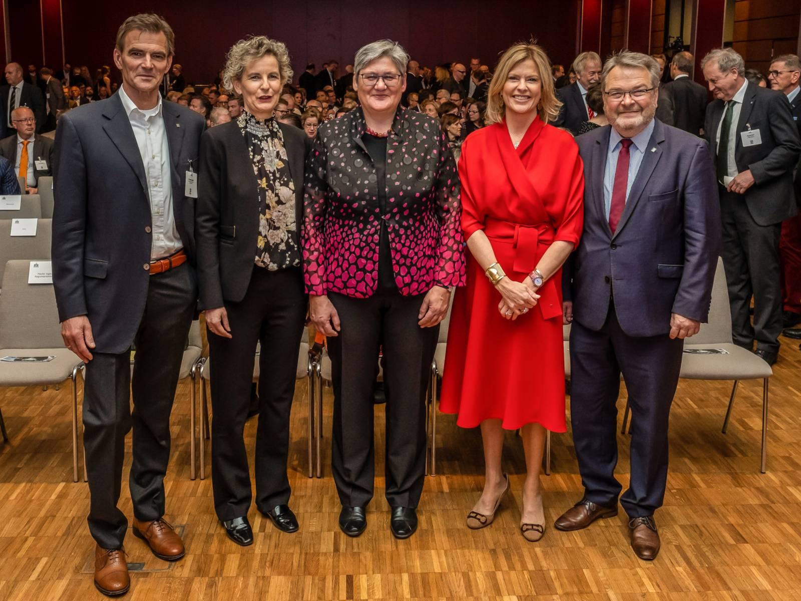 Fünf Personen in einem großen Saal