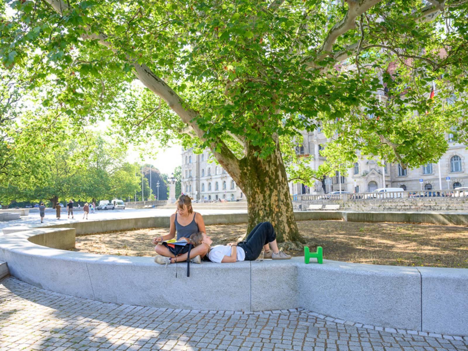 Zwei Personen auf einer Steinfläche. Dahinter ein Baum.
