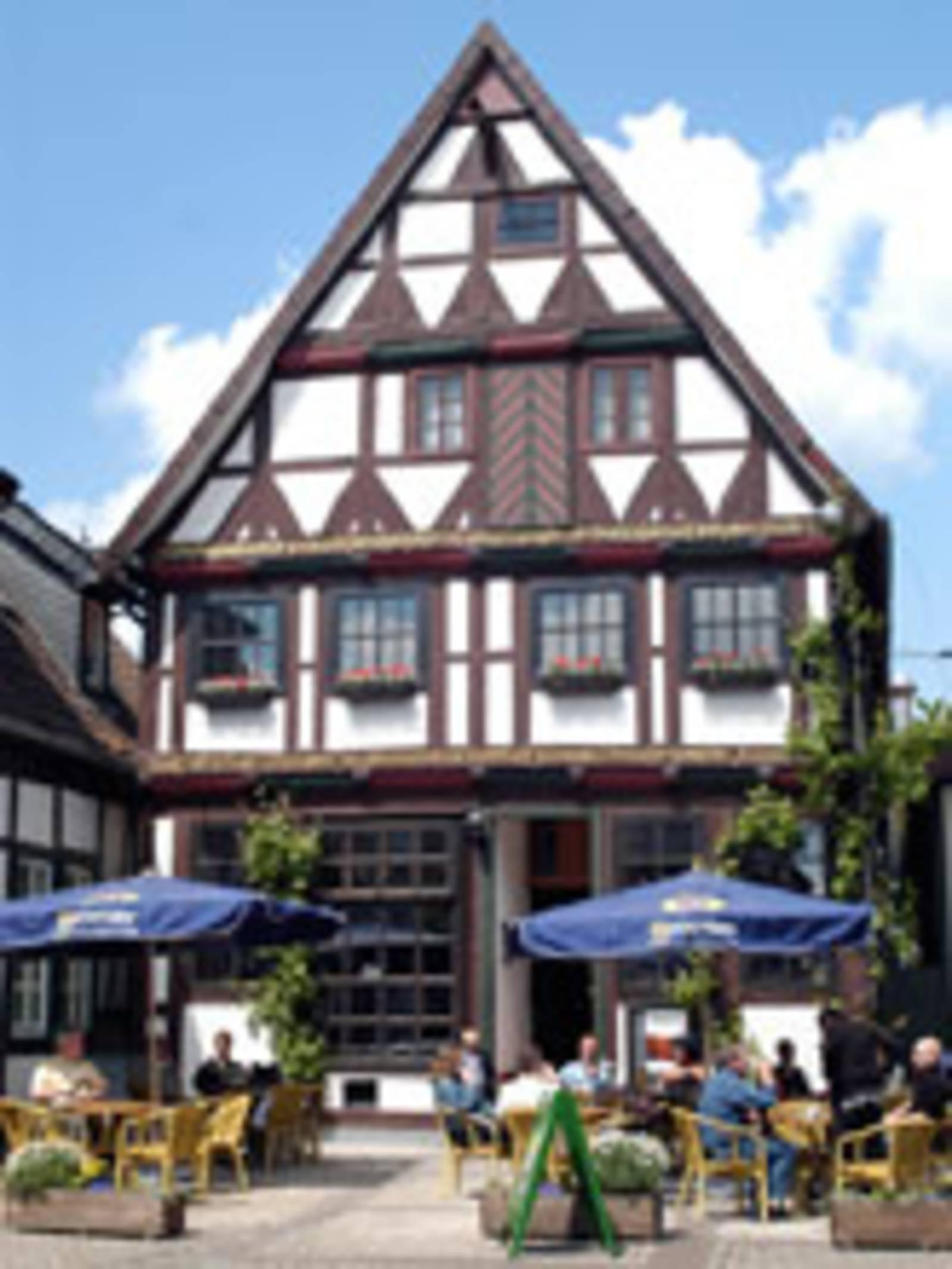 Schmales Fachwerkhaus mit braunen Fenstern. Vor dem Haus sitzen Menschen unter blauen Sonnenschirmen.