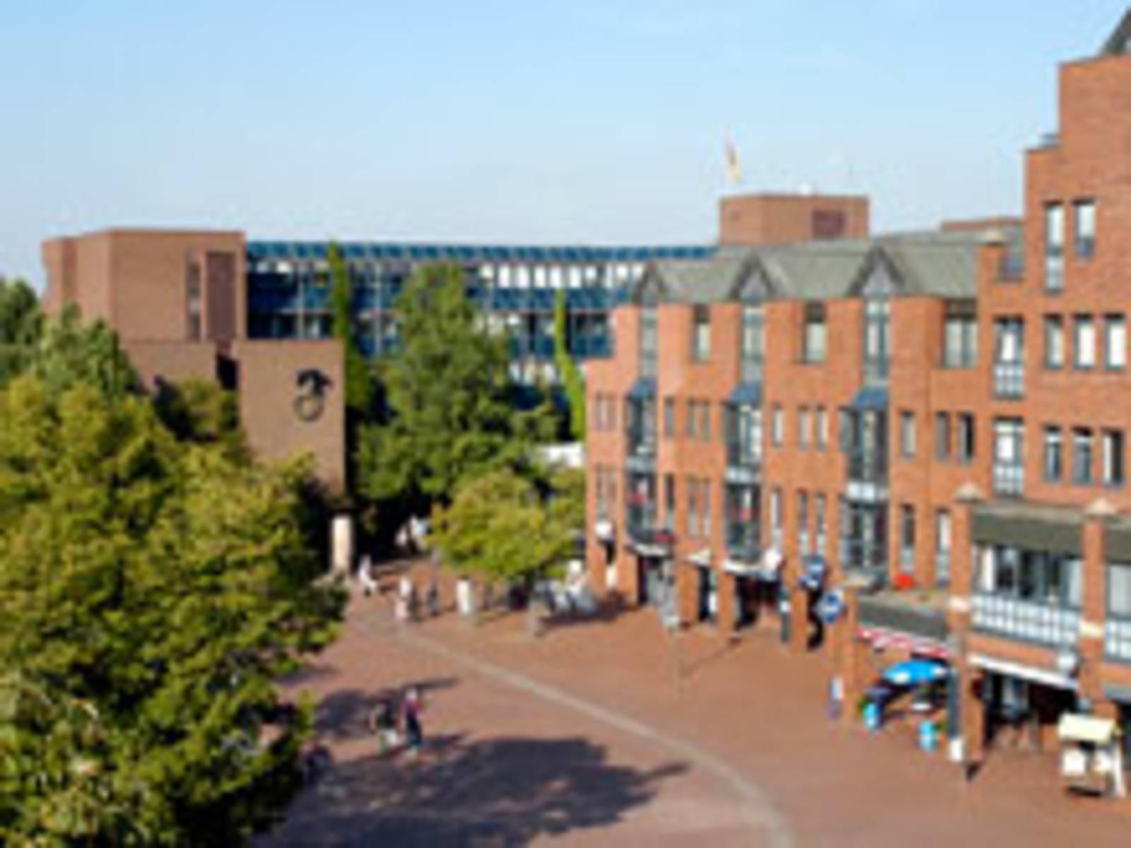 Mehrere aneinander gereihte Gebäude mit roter Fassade. Im Erdgeschoss befinden sich Ladenzeilen. Der Fußgängerbereich ist rot gepflastert.