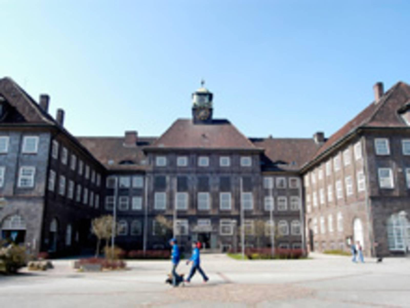 Gebäude in U-Form mit sechs Fahnenmasten davor, sowie zwei Rasenflächen mit kleinen Hecken.