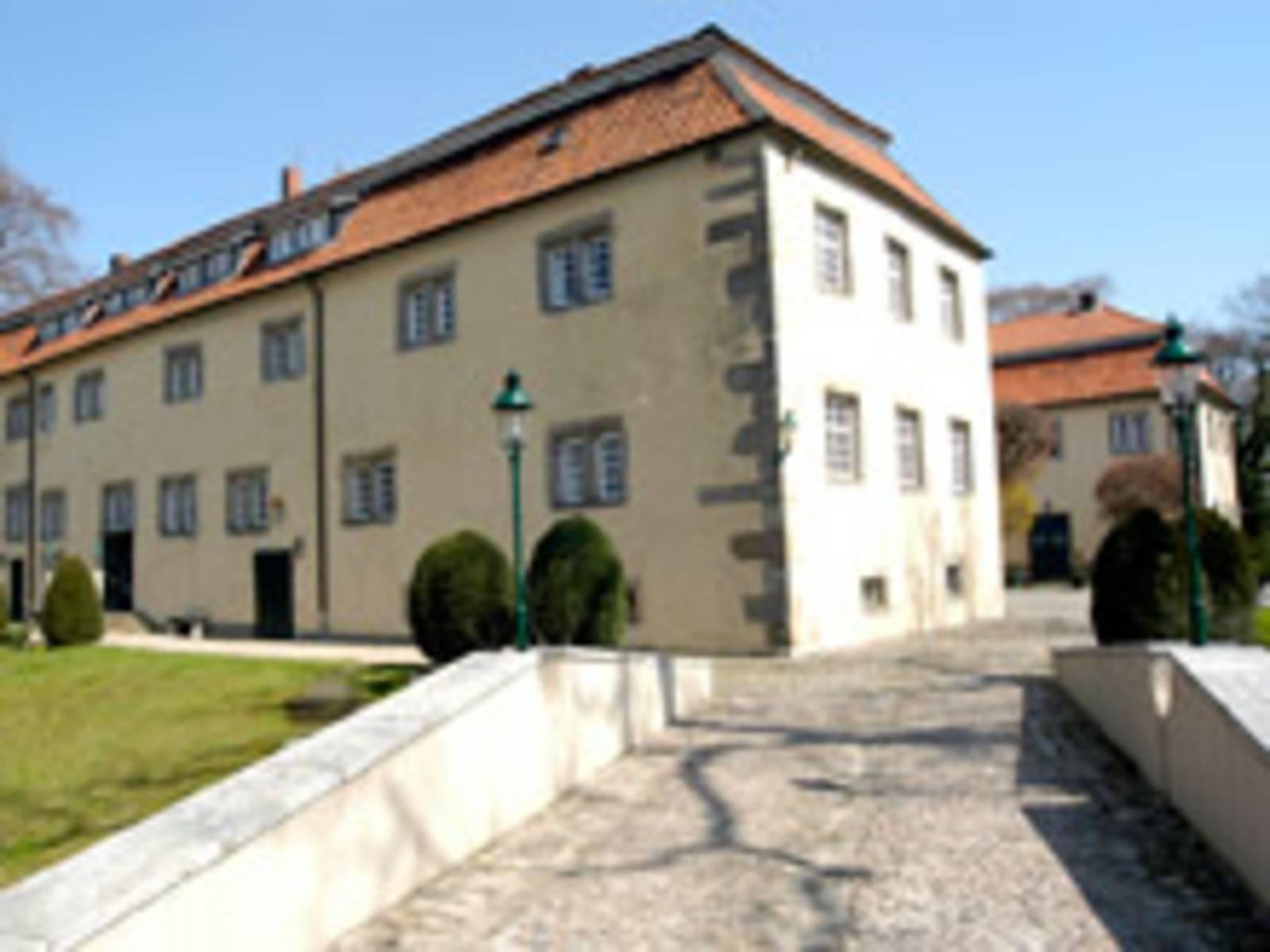 Fußweg mit Pflastersteinen der rechts und links von einer kniehohen Mauer eingefasst ist. Der Weg führt auf zwei parallel stehende Gebäude zu.