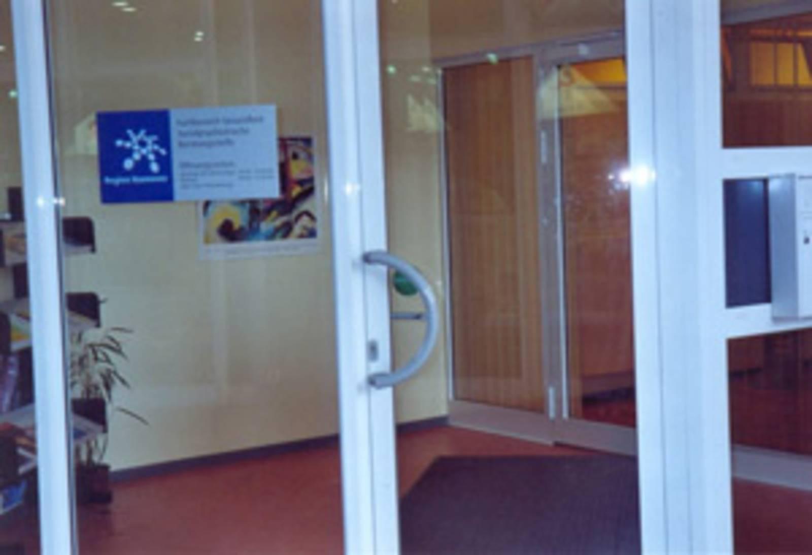 Eingang aus Glastüren mit weißem Rahmen und Türgriff, durch die Glasfront sieht man die dahinter liegenden Räume