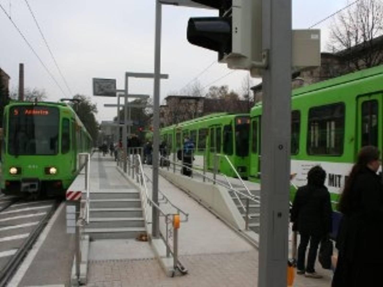 Zwei Straßenbahnen an einem Hochbahnsteig.