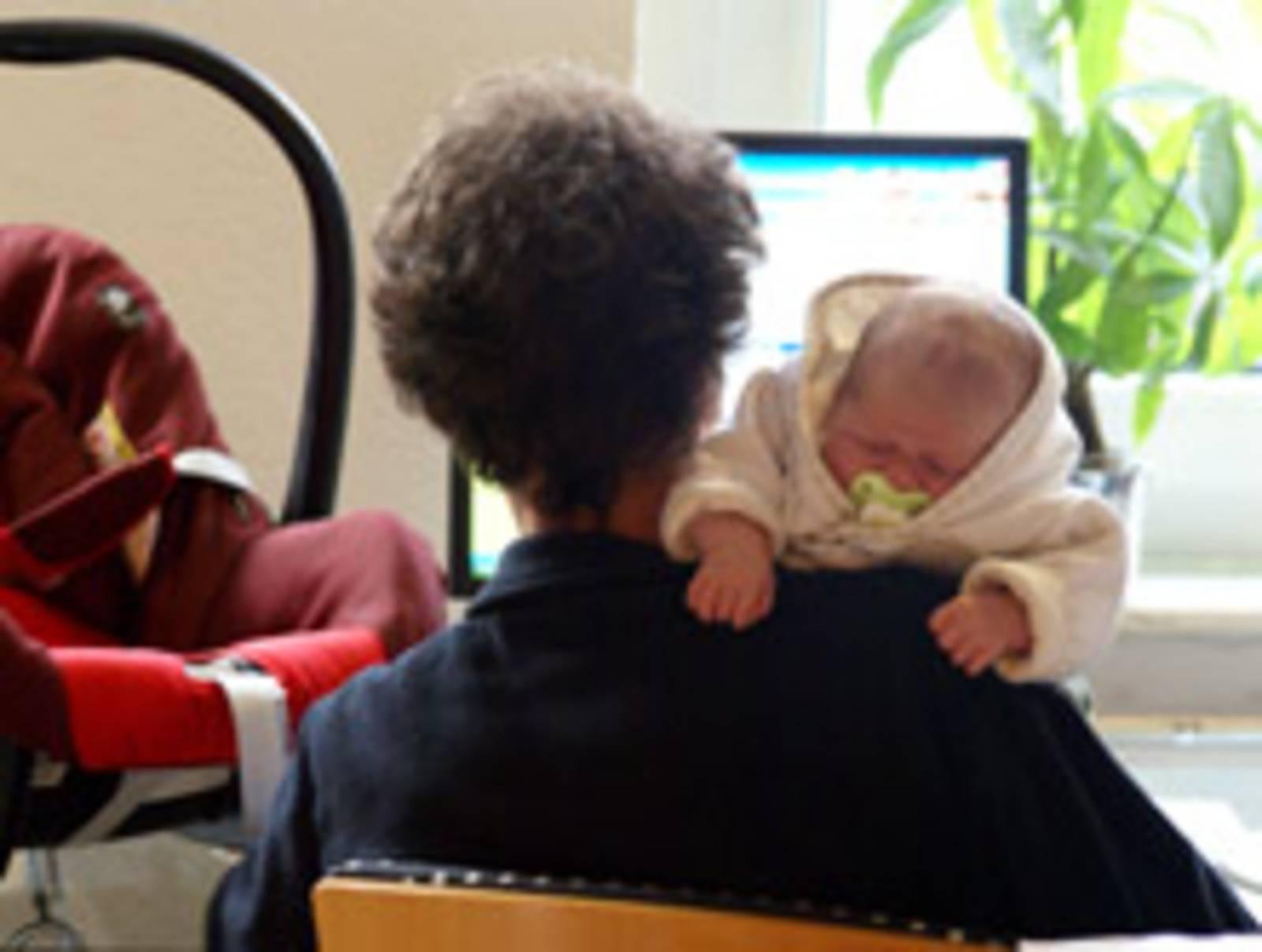 Schlafendes Baby mit PC im Hintergrund
