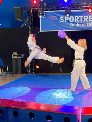 Zwei junge Menschen bei einer Art Kampfsport. Einer springt gerade durch die Luft und versucht, mit seinem Fuß einen Luftballon zu treffen, den die andere Person festhält