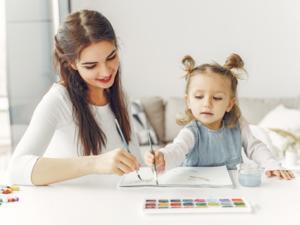 Eine Frau und ein Kind malen gemeinsam ein Bild mit Pinseln