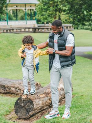 Ein Kind läuft über einen Baumstamm, der Vater hält es dabei an den Händen