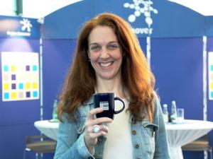 Eine Frau mit langen, roten Haaren steht lächelnd vor zwei Stehtischen und einer blauen Ausstellungswand. In der rechten Hand hält sie eine Tasse mit dem Logo der Matinee im Foyer auf Brusthöhe vor sich.