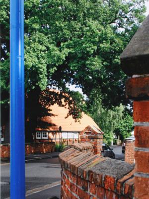 blaue Markierungssteele mit roter Ziegelmauer, im Hintergrund ein rotes Bauernhaus