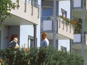 Eine Familie auf dem Balkon eines Mehrfamilienhauses, im Hintergrund weitere Balkone