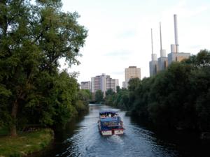 Ein Ausfllugsboot auf der Ihme, im Hintergrund die Stadtwerke und da Ihmezentrum