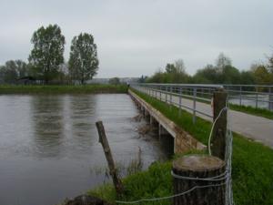 Hochwasser führender Fluss und eine nicht überschwemmte Brücke