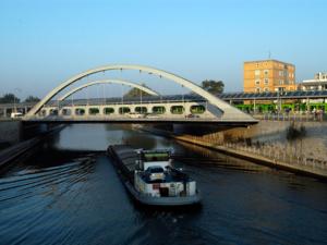 Brücke, auf der Autos und eine grüne Stadtbahn fahren, über den Mittellandkanal, ein Frachtschiff auf dem Kanal, in Richtung Brücke fahrend