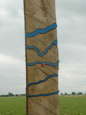 Senkrecht stehender Holzbalken mit blauen Metallwellen, die ein größeres Gewässer symbolisieren