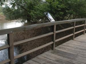 Metalltafel, die am Geländer einer Holzbrücke befestigt ist