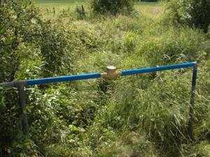 Wasseruhr, auf blauen Stahlrohren montiert, über einem Bach