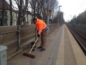 Auf dem Bild ist ein Mann zu sehen, der mit einem Besen den Bahnsteig reinigt.
