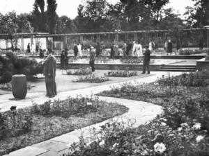 Historische Aufnahme des Stadtparks aus 1951: Flanierende Besucher zwischen terrassenförmig angelegten Blumenbeeten.