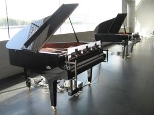 Zwei Klaviere stehen hintereinander in einem Raum.
