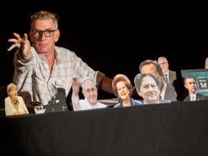 Mann auf Bühne mit diversen Politiker-Portraits.