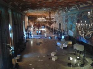 Das barocke Galeriegebäude vom Balkon ausgesehen; Besucher laufen durch die Videoskulptur von caprificus.org. Weiße Blätter liegen auf dem Boden.