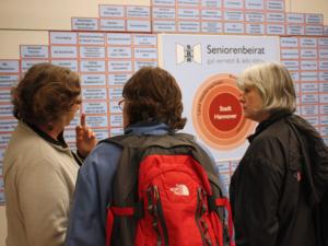 Drei Damen diskutieren vor einer Wand mit der Übersicht ehrenamtlicher Tätigkeiten von Seniorinnen und Senioren in Hannover