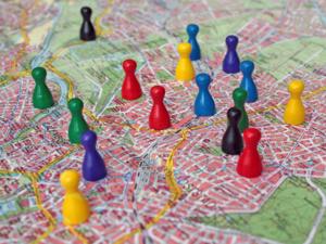 Symbolbild: Verschiedenfarbige Spielfiguren stehen auf dem Stadtplan von Hannover.