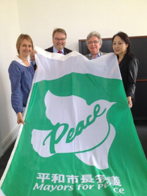 Evelyn Kamissek, Thomas Hermann, Michel Cibot und Miho Cibot mit der Flagge von Mayors for Peace