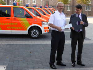 Feuerwehrdezenent Dr. Marc Hansmann übergibt den symbolischen Schlüssel für sechs neue Notarzteinsatzfahrzeuge an Feuerwehrchef Claus Lange.