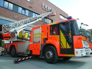 Die Drehleiter der Feuerwehr unterstützt bei der Installation des Schriftzuges am neuen Wachgebäude