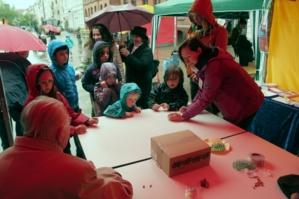 Kinder probieren gemeinsam mit Senioren das Murmelspielen aus.