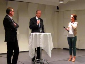 Drei Personen stehten um einen Stehtisch auf einer Bühne. Die mittlere Person spricht in ein Mikrofon, das sie in der Hand hält. Die linke Person verschränkt die Arme vor der Brust, die rechte hält ebenfalls eine Mikrofon in der Hand und schaut zur sprechenden Person in der Mitte.