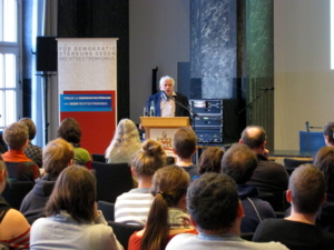 Der Referent steht oben im Bild am Rednerpult. Vor ihm sieht man ca. 14 Zuhörer/innen von hinten.