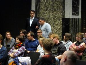 Der Moderator hält einem Mann in der hintersten Reihe das Mikrofon ins Gesicht, während der Mann spricht. Die anderen sitzenden Zuhörer/innen drehen sich zu ihm um.