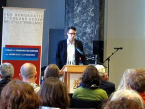 Ein Mann mit Brille steht am Rednerpult. Links neben ihm steht eine Stellwand mit dem Logo der Stelle für Demokratiestärkung und gegen Rechtsextremismus. Vor ihm sieht man etwa zehn der sitzenden Zuhörerinnen von hinten.