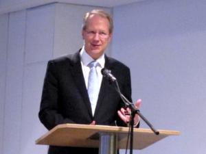 Ein Mann steht hinter einem Rednerpult und spricht in ein Mikrofon.