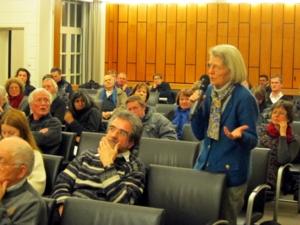 Foto einer Besucherin, die während der Diskussion ihren Redebeitrag ins Mikrofon spricht