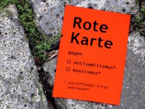 """Ein roter Handzettel mit der Aufschrift """"Rote Karte gegen Antisemitismus"""" liegt auf dem Kopfsteinpflaster"""