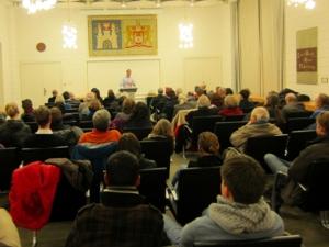 Foto mit Blick von hinten durch den Gobelin-Saal aufs Publikum