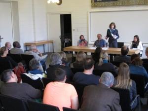 Etwa 30 Personen sitzen in Stuhlreihen und blicken nach vorn zum Redner/innenpult, an dem die Rednerin steht.