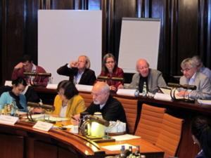 Acht Personen in zwei Sitzreihen des Hodlersaals. Die externen fünf Expert/innen sitzen in der hinteren Reihe, drei Ausschussmitglieder in der vorderen.