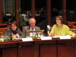 Ein Mann und zwei Frauen sitzen im Hodlersaal hinter schweren Sitzungspulten, in der dunklen Fensterfront hinter ihnen spiegeln sich die anderen Mitglieder des Ausschusses.