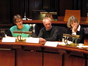 Drei Personen - zwei Frauen und ein Mann - sitzen im Hodlersaal in einer Sitzreihe hinter Pulten und blicken nach rechts. Auf den Pulten vor ihnen stehen Namensschilder.