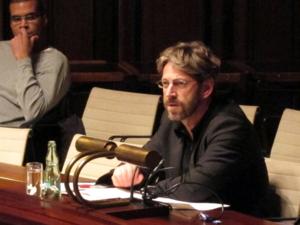 In der Mitte des Bildes sitzt eine Person mit Brille und Bart in einer Sitzreihe im Hodlersaal und spricht. Links oben im Hintergrund sitzt eine weitere Person und hört ihm zu.