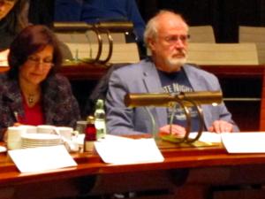 Zwei Personen – eine Frau und ein Mann – sitzen im Hodlersaal hinter Pulten. Vor ihnen stehen Namensschilder.