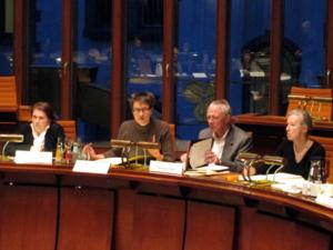 Vier Personen sitzen in einer nach innen gebogenen Reihe hinter einem langen Pult im Holdersaal. Jeschke hebt den Zeigefinger und spricht, T. Walter schaut in einen Aktenordner auf dem Tisch vor ihm. Auf den Tischen stehen Namensschilder.
