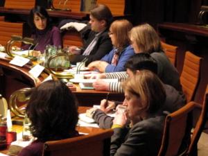 Sieben Personen sitzen an zwei gebogenen Pulten. Die vier oberen schauen auf ein Papier, das vor Kelich (auch oben im Bild) auf den Tisch liegt. Die drei anderen schauen auf Papiere, die vor ihnen auf dem Tisch liegen.